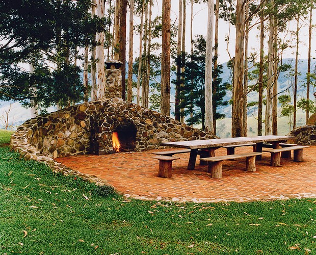 Lareira externa | Para fazer as refeições ao ar livre, o arquiteto criou o espaço com mesa e bancos de madeira instalados sobre piso de tijolos (Foto: Marco Antonio/Editora Globo)