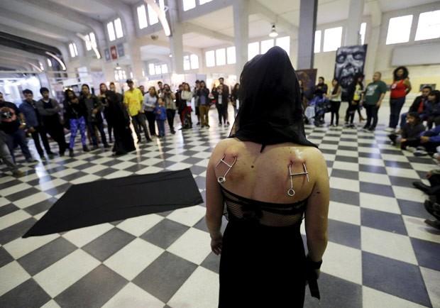 Imagem mostra ganchos colocados nas costas de mulher durante evento de suspensão corporal (Foto: Rodrigo Garrido/Reuters)