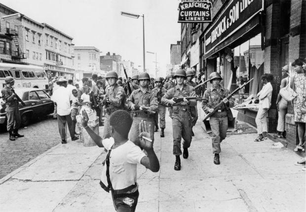 1967 - Um garoto negro corre da Guarda Nacional, no Estado de Nova Jersey. O boato da morte de um taxista negro, por policiais, deflagrou uma revolta popular que durou cinco noites  (Foto: Don Hogan Charles/The New York Times)