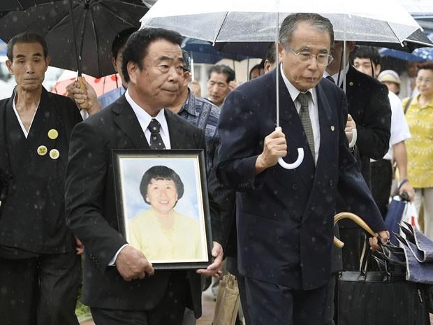 Mikio Watanabe segura foto de sua mulher, Hamako, que se matou em 2011 após ter que deixar sua casa devido ao acidente nuclear de Fukushima. A família processou a operadora da usina nuclear, e ganhou o direito a uma indenização em decisão nesta terça-feira (26) (Foto: Kyodo/Reuters)