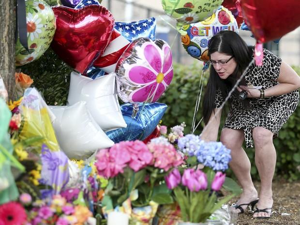 Mulher coloca flores em um memorial em frente à sede da WDBJ7 em Roanoke, Virgínia, nos EUA. Dois jornalistas da emissora foram mortos durante uma transmissão ao vivo após serem baleados por Vester Flanagan, um ex-funcionário da TV  (Foto:  Chris Keane/Reuters)