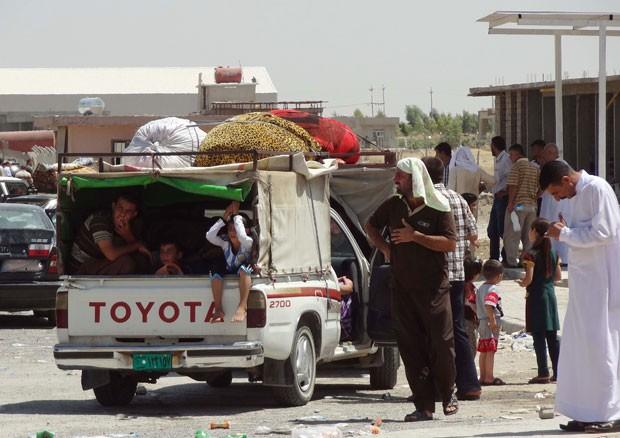 Curdos xiitas do Iraque, deslocados pelo avanço jihadista, esperam em estrada entre Kirkuk e Erbil pra deixar a região nesta sexta-feira (8) (Foto: Marwan Ibrahim/AFP)