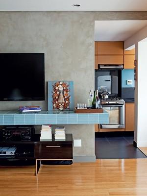 , a parede que separa a cozinha da sala é revestida de tecnocimento, da ns Brazil. em torno dela, a bancada de concreto recebeu azulejos da linha retrô, da Pavão revestimentos (Foto: Edu Castello)