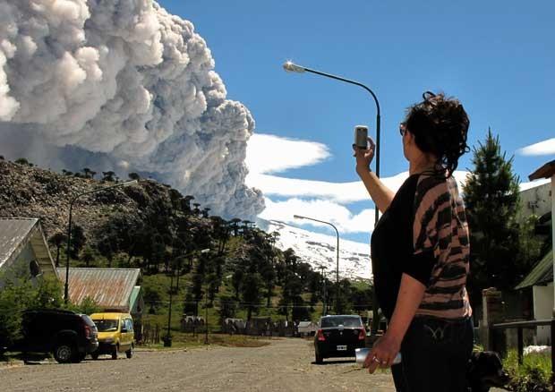 Mulher fotografa fumaça do vulcão Copahue em Caviahue, Argentina, neste sábado (22) (Foto: AFP)