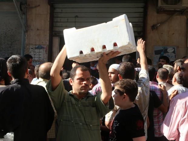 Homem carrega caiza com vegetais que recebeu nesta quarta-feira (10) em Aleppo, na Síria (Foto: REUTERS/Abdalrhman Ismail)