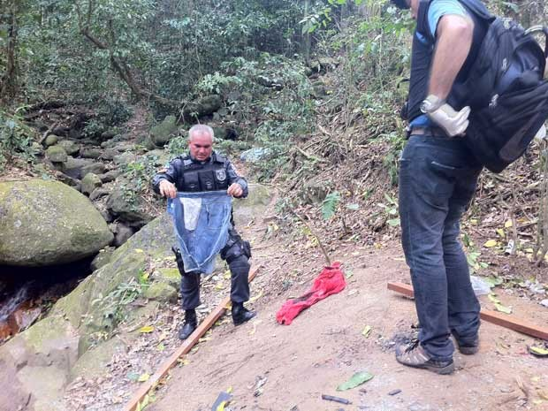 Policiais encontraram roupas próximo a cachoeira, nesta quinta (13)  (Foto: Janaína Carvalho/G1)