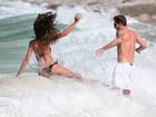 Izabel Goulart leva caldo e quase perde o biquíni em dia de praia