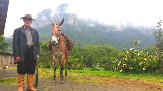 O tropeiro Joaquim Lorenzoni, com sua mula Estrela, mostra a trilha que liga o sul à serra. (Foto: Lívia Andrade/RBS TV)