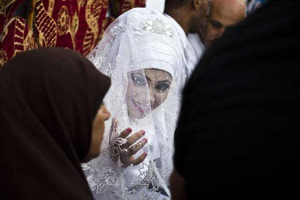 Heba Fayad, de 23 anos, é vista durante seu casamento em uma escola da ONU em Gaza nesta quarta-feira (13) (Foto: Roberto Schmidt/AFP)