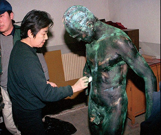 An assistant paints the body of Life Sculpture artist Wang Deshun before a performance in Beijing Tuesday December 10, 1996. Wang, a sixty-year-old former actor, performs almost naked in poses influenced by the sculptures of Rodin. (AP Photo) (Foto: Associated Press)