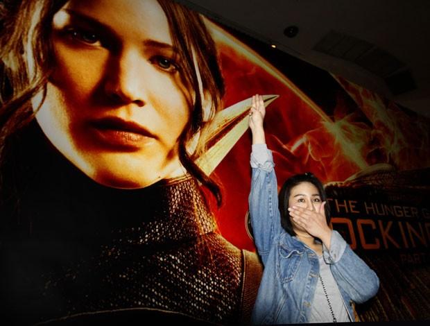Nachacha Kongudom, faz saudação com três dedos usada no filme 'Jogos Vorazes' em frente a cinema em Bangcoc, na Tailândia, nesta quinta-feira (20); ela foi detida pelo gesto, adotado pelos opositores ao golpe militar ocorrido em maio no país (Foto: Sakchai Lalit/AP)