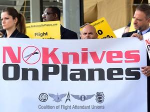 Comissários de bordo e funcionários de companhias aéreas protestam no Aeroporto de Los Angeles contra novas regras que permitem levar canivetes, facas e tacos de beisebol em aviões nos EUA (Foto: Frederic J. Brown/AFP)