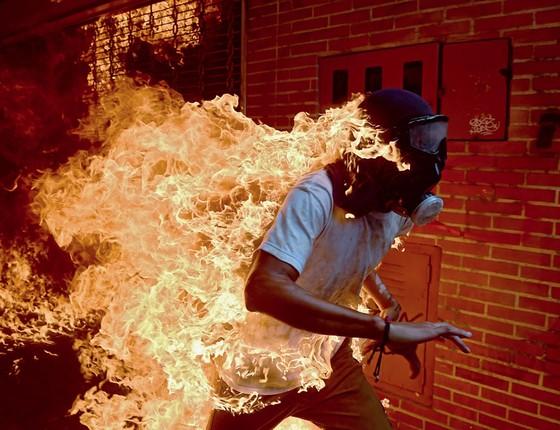 Um manifestante é atingido  pelo fogo  em Caracas,na quarta-feira,dia 03 (Foto: RONALDO SCHEMIDT/AFP)