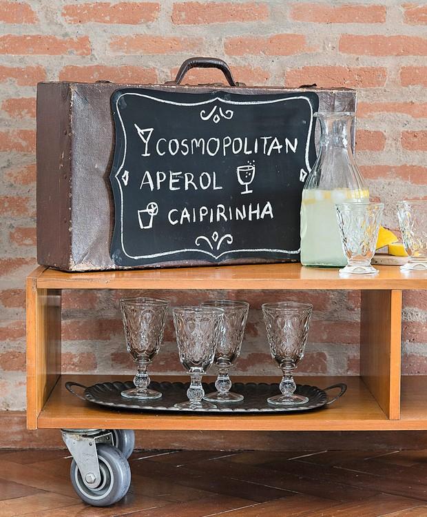 O look surrado é o charme da mala Ella Arts, usada como lousa do barzinho. Copos e jarra Tok & Stok (Foto: Cacá Bratke / Editora Globo)