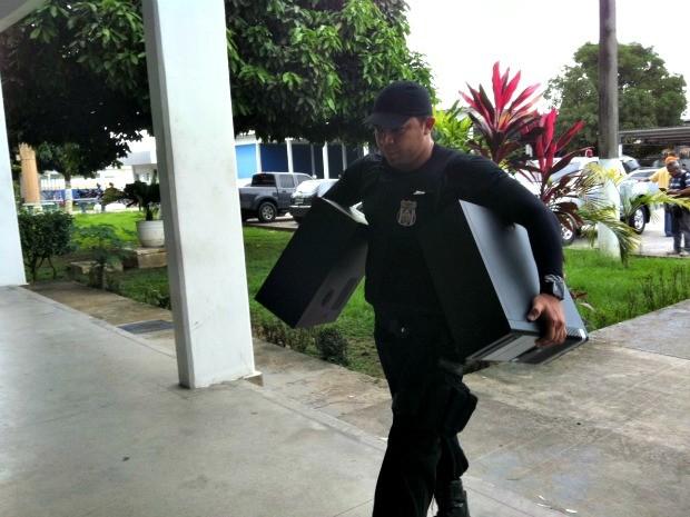 Policial carrega computadores apreendidos durante a Operação Gaia (Foto: Girlene Medeiros /G1 AM)