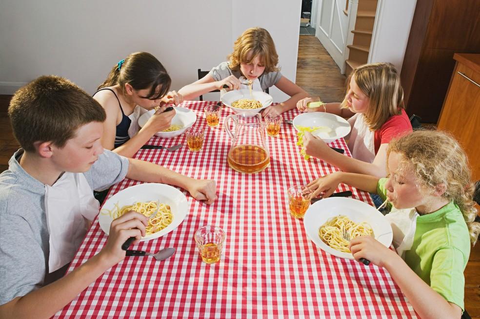 Crianças comendo macarrão (Foto: Frank Herholdt/Image Source)