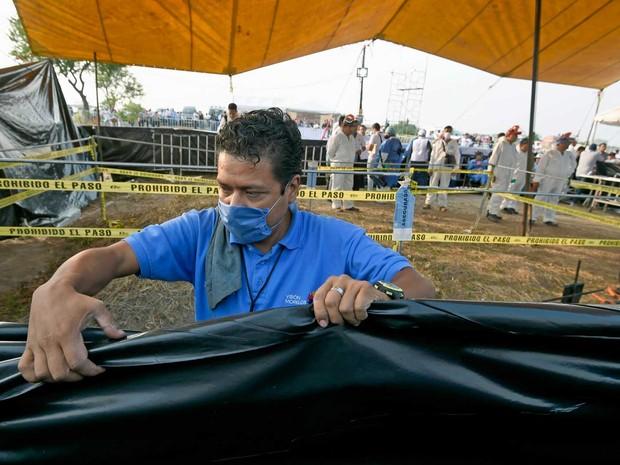 Homem preparar um dos 116 corpos encontrados em uma vala comum em Morelos, México (Foto: Alfredo Estrella / AFP Photo)