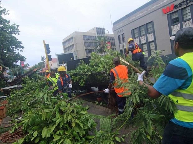 Trabalhadores tentam desimpedir ruas tomadas por árvores que foram arrancadas pela tormenta que atingiu Fiji (Foto: Steven Sapphire / Reuters)
