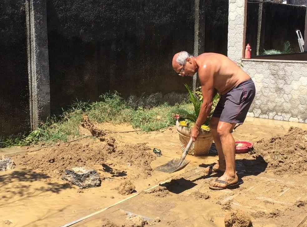 Após rompimento, moradores começaram limpar quintal das casas alagadas (Foto: Matheus Rodrigues/G1)