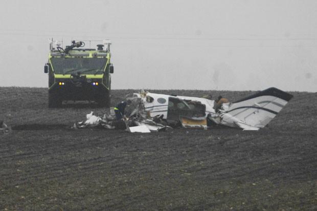 Investigadores trabalham no local da queda de um avião de pequeno porte em Illinois, nos EUA; as sete pessoas a bordo morreram (Foto: The Pantagraph, David Proeber/AP)