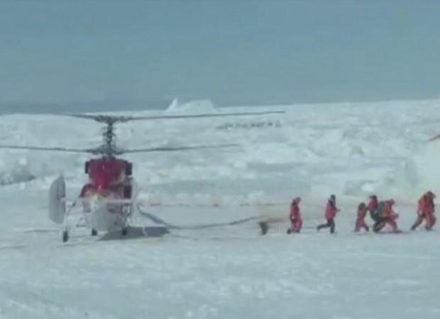Equipe de resgate deixa helicóptero para verificar condições de saída de navio no gelo (Foto: Chris Turney/Reuters)
