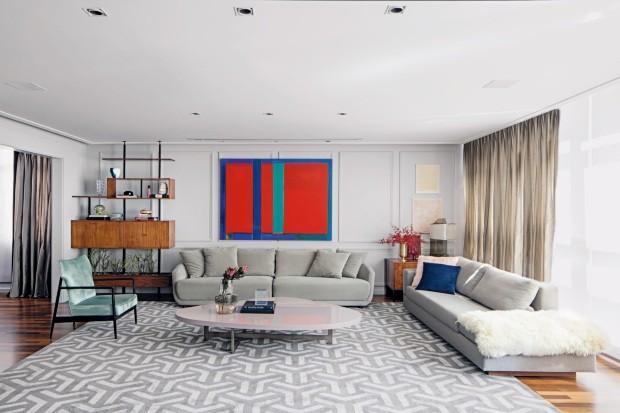 A tela de André Ricardo, na Galeria Pilar, traz cor ao espaço em que as paredes cinza-claras apresentam boiseries de gesso da Casa Franceza. O sofá ao centro é da Artefacto e o outro, da Vermeil (Foto: Gui Morelli / Divulgação)