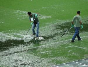 Funcionários da Minas Arena tiram água do campo com rodo no Mineirão (Foto: Tarcísio Badaró)