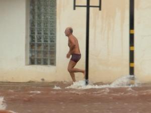 Homem tirou a roupa para não enrroscar na enxurrada (Foto: Reprodução/TV TEM)