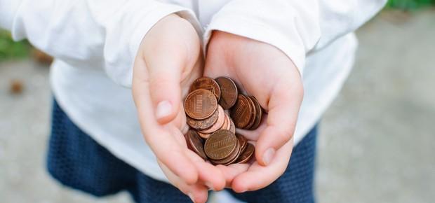 Mãos de criança segurando moedas (Foto: Shutterstock)