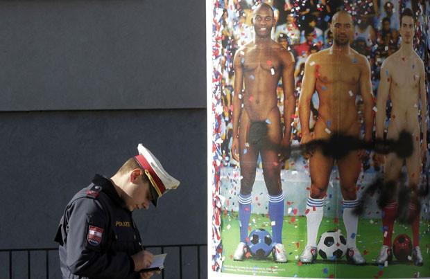 Policial passa por um pôster pichado em Viena, em protesto à exposição de genitálias masculinas nos anúncios colocados em vias de Viena (Foto: Herwig Prammer/Reuters)