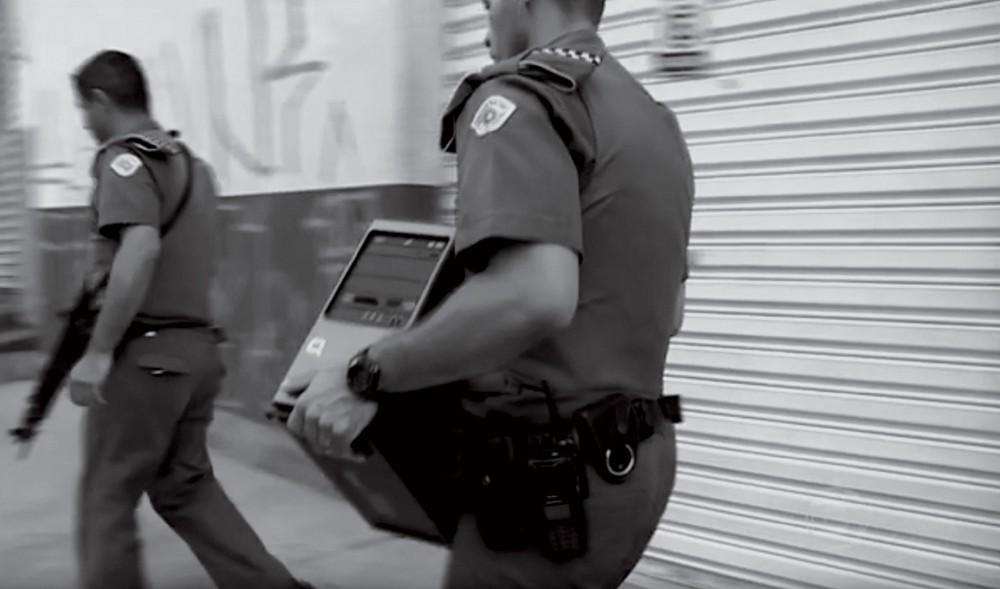 Policiais carregam o computador de um dos investigados por crime de racismo (Foto: Reprodução)