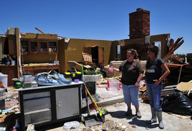 Tammy Wade (esquerda) observa, ao lado da cunhada Dana Givens, o que sobrou de sua casa em El Reno, Oklahoma (Foto: Nick Oxford/AP Photo)