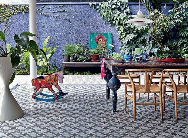 Coberta por ladrilhos hidráulicos, a sala de jantar fica na área externa. As folhagens cobrem o muro roxo. Projeto da arquiteta e paisagista Daniela Ruiz (Foto: Victor Affaro/Editora Globo)