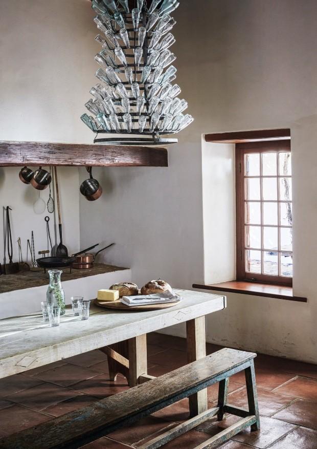 Detalhe. A enorme mesa de refeitório é onde todos se reconectam. Destaque para o candelabro feito a partir de um secador de garrafas de vinho (Foto: Greg Cox / Bureaux)