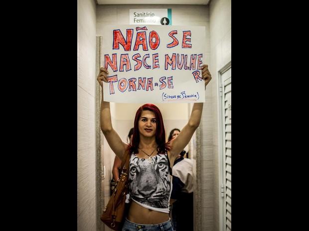 Participante do protesto ergue cartaz em frente ao banheiro feminino do Shopping Center 3, na Avenida Paulista (Foto: Cris Faga/Fox Press Photo/Estadão Conteúdo)