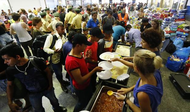 Voluntários servem refeição para os refugiados que chegam à estação de Munique, na Alemanha  (Foto: Matthias Schrader/ AP)