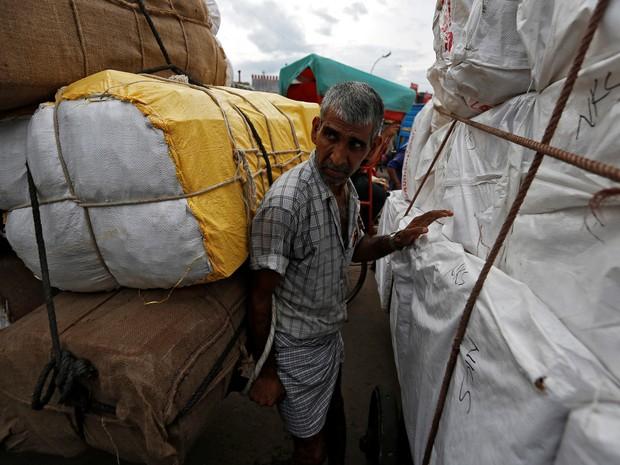 Trabalhador carrega sacos de brinquedos em um mercado de Delhi, na Índia, na terça-feira (2) (Foto: REUTERS/Adnan Abidi)
