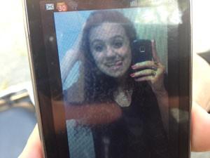 Tia mostra no celular a foto de jovem vítima de homicídio. (Foto: Julia Basso Viana /G1))