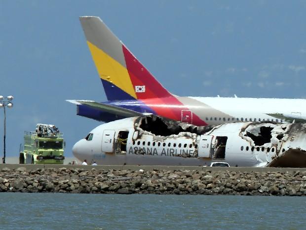 Aeronave da Asiana Airlines passa ao lado do Boeing 777 que se acidentou no dia 6 de julho no Aeroporto de San Francisco. (Foto: Justin Sullivan/Getty Images/AFP)