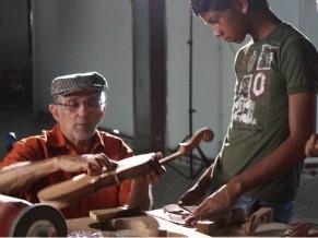 Mestre Ari, do Instituto AMA, ensina jovem de Bragança a construir rabeca no projeto Sons do Caeté (Foto: Divulgação / Christina Fuscaldo)