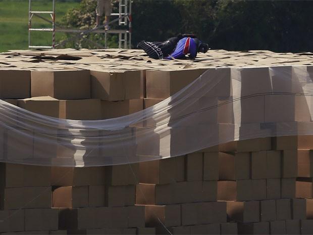 Gary Connery, usando uma veste especial, aterrissa com sucesso em um conjunto de mais de 18 mil caixas de papelão após pular de 731 metros de altitude sem usar pára-quedas (Foto: Reuters)