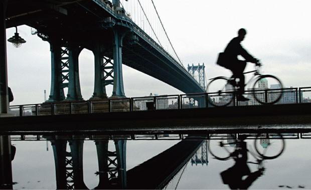 PASSEIO  Um ciclista pedala perto da Manhattan Bridge, em NY. Eles veem o melhor da cidade  (Foto: Shannon Stapleton/Reuters)