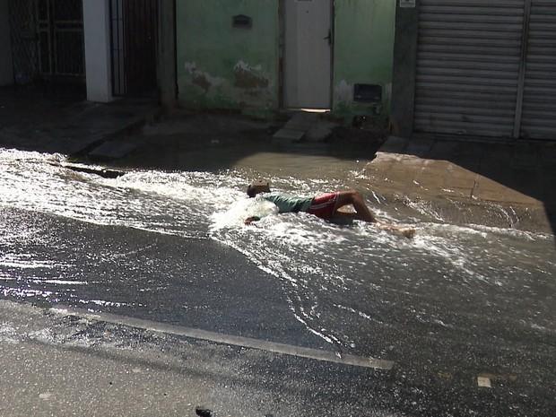 Crianças brincou enquanto a água vazava na avenida Almirante Barroso (Foto: Reprodução/TV Paraíba)