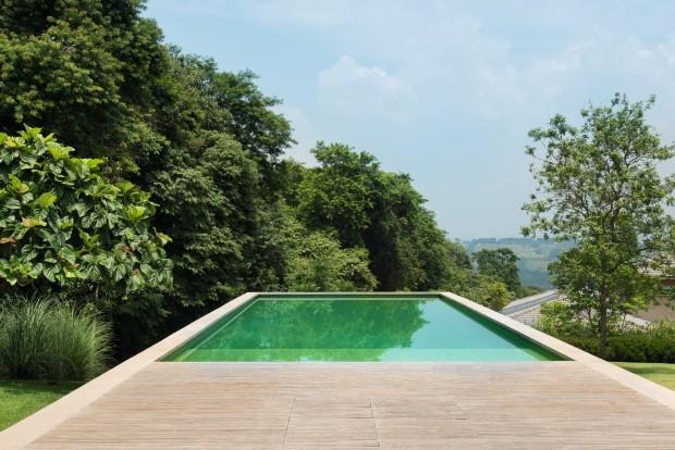 Construída em um grande volume de concreto, a piscina se projeta ao longo do declive do terreno e parece flutuar. As árvores mais altas pertencem a uma área de preservação ambiental do condomínio (Foto: Cacá Bratke / Editora Globo)