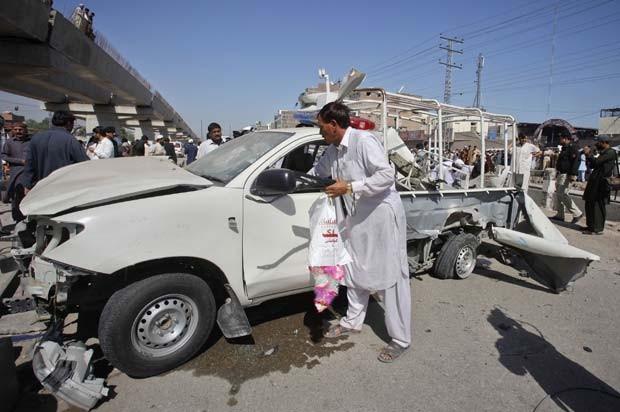 Perito recolhe provas em carro destruído por bomba neste sábado (12) em Peshawar, no Paquistão (Foto: Reuters)