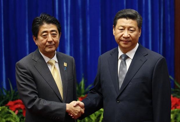O primeiro-ministro japonês, Shinzo Abe, e o presidente chinês, Xi Jinping, apertam as mãos em encontro durante o Fórum de Cooperação Econômica Ásia Pacífico (APEC), em Pequim, na China, nesta segunda-feira (10) (Foto: Kim Kyung-Hoon/Reuters)
