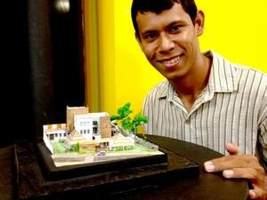 André Figueira pousa ao lado de sua maquete para dar a referência do tamanho do seu trabalho (Foto: Eduardo Duarte / G1)