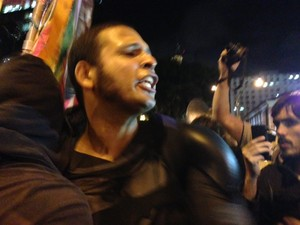 Eron Melo, o Batman, tira a máscara e depois a coloca novamente em protesto no Rio (Foto: Isabela Marinho/G1)