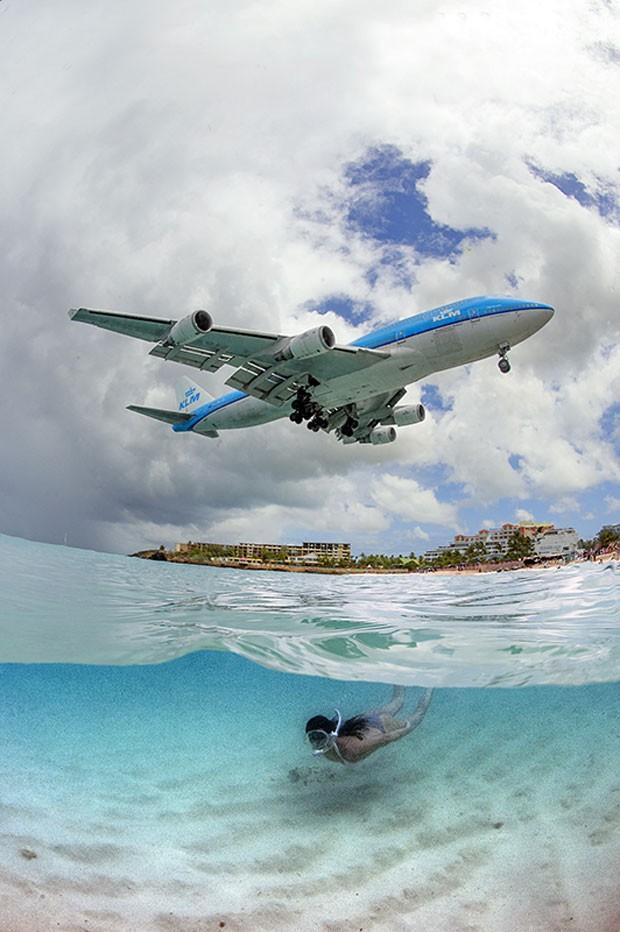 Foto de Daniel Botelho mostra mulher mergulhando em St. Maarten, no Caribe, enquanto avião sobrevoa a ilha (Foto: Daniel Botelho/Divulgação)