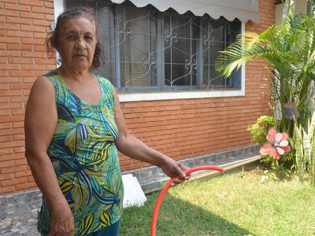 Maria Pimenta, 69 anos, levanta cedo para armazenar a água da rua em baldes para utilizar durante o dia (Foto: Adriano Oliveira/G1)